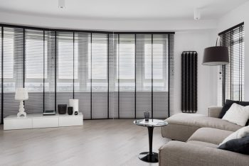 Elegant living room with round window wall with black window blinds, and stylish furniture